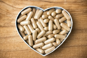 Herbal drug capsules, a heart-shaped box. Wooden surface. Alternative medicine concept.